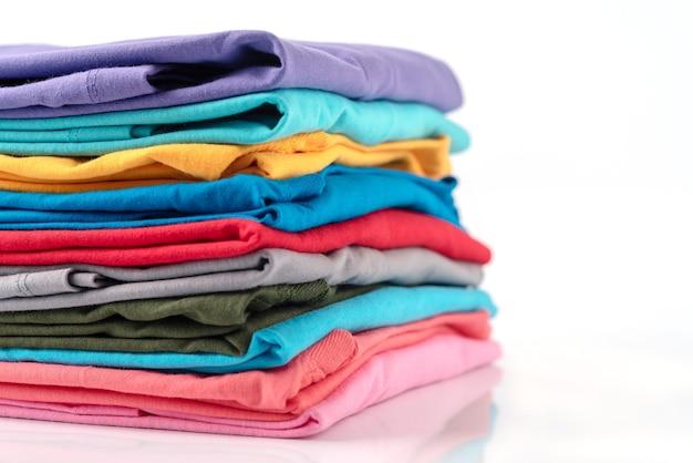 Pilha de t-shirt de algodão colorido isolada no fundo branco.