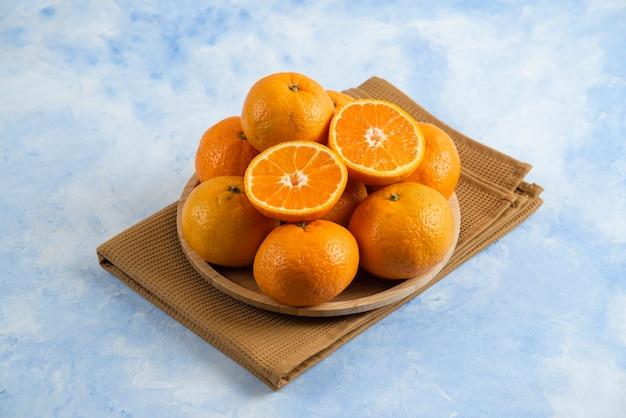 Pilha de tangerina clementina e placa de madeira sobre a toalha