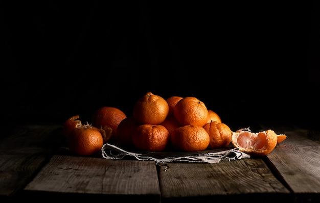 Pilha de tangerina laranja madura com casca redonda em um prato em uma superfície preta