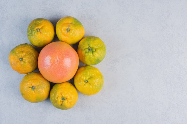 Pilha de tangerinas ao redor de toranja em fundo cinza.