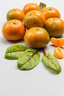 Pilha de tangerinas com folhas de acelga