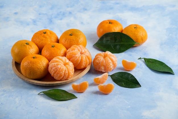 Pilha de tangerinas de clementina orgânica descascadas ou inteiras