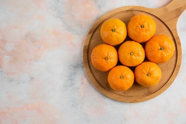Pilha de tangerinas de clementina sobre uma tábua de madeira