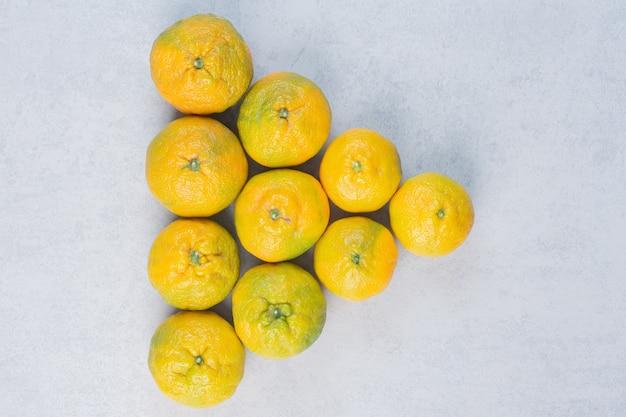 Pilha de tangerinas sobre fundo cinza.