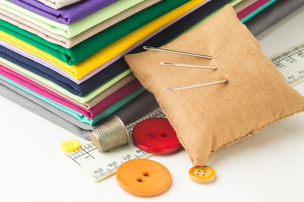 Pilha de tecido com agulhas e botões