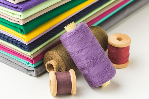 Pilha de tecido com carretéis de linha