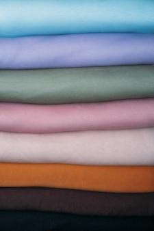 Pilha de tecidos de cor pastel natural sobre tecidos de fundo branco e roupas organizadas de forma organizada