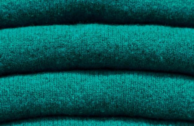Pilha de tendência quetzal verde camisolas de lã close-up