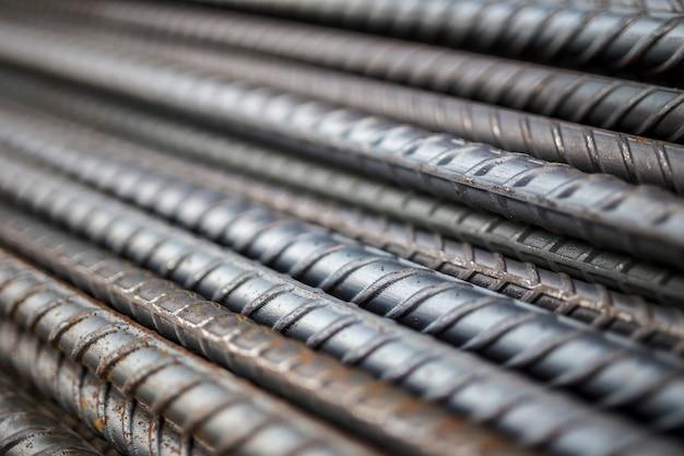Pilha de textura da barra de aço no canteiro de obras para o fundo.