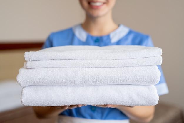 Pilha de toalhas brancas macias, seguras por uma jovem dona de casa ou camareira sorridente dentro do quarto do hotel