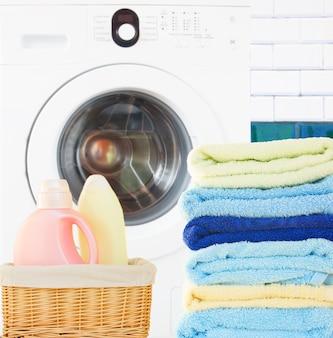 Pilha de toalhas coloridas com detergente e máquina de lavar no banheiro