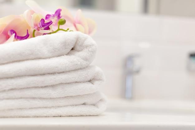 Pilha de toalhas com decoração de flores em um quarto de hotel