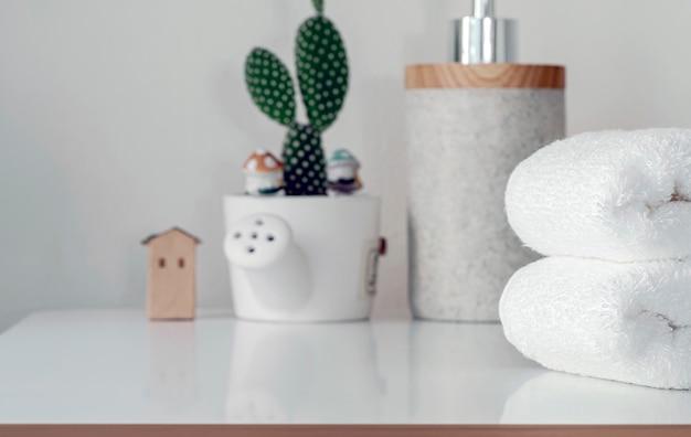 Pilha de toalhas de banho brancas dobradas na tabela superior branca, espaço da cópia.