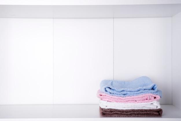 Pilha de toalhas de banho coloridas sobre fundo claro