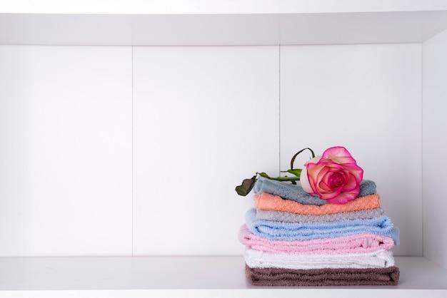 Pilha de toalhas de banho com rosa sobre fundo claro