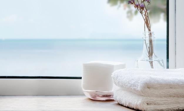 Pilha de toalhas de banho limpas na mesa de madeira perto da janela com vista do mar. copie o espaço.