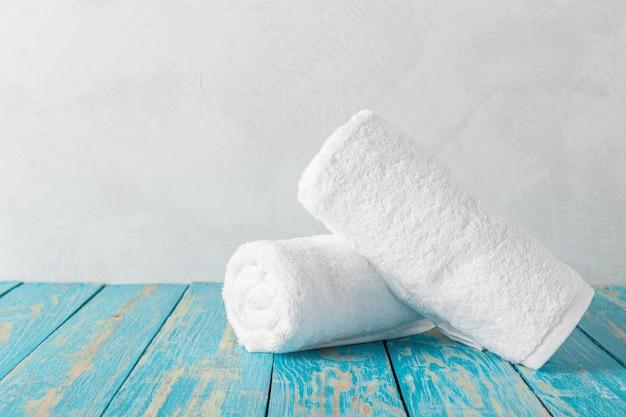 Pilha de toalhas de banho na mesa de madeira com espaço de cópia