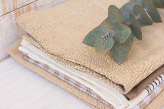 Pilha de toalhas de cozinha de linho e algodão na mesa da cozinha de madeira branca com ramo de eucalipto