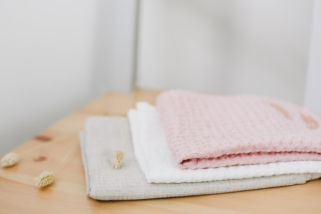 Pilha de toalhas de linho de algodão limpas na mesa da cozinha. cores pastel