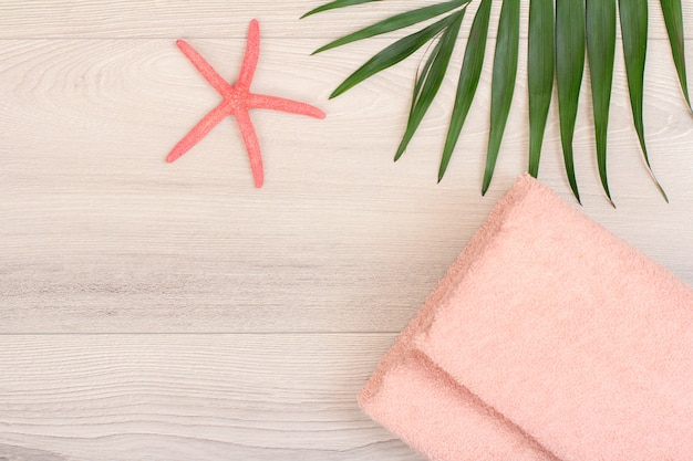 Pilha de toalhas de terry macias com estrela do mar e folha verde sobre fundo de madeira. produtos de spa. vista do topo.
