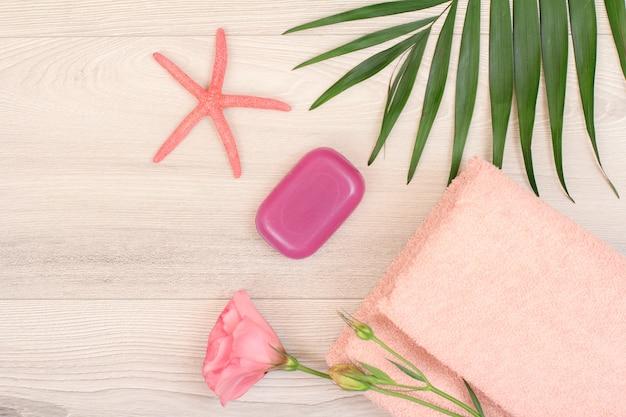 Pilha de toalhas de terry macias com flor rosa, sabonete, estrela do mar e folhas verdes sobre fundo de madeira. produtos de spa. vista do topo.