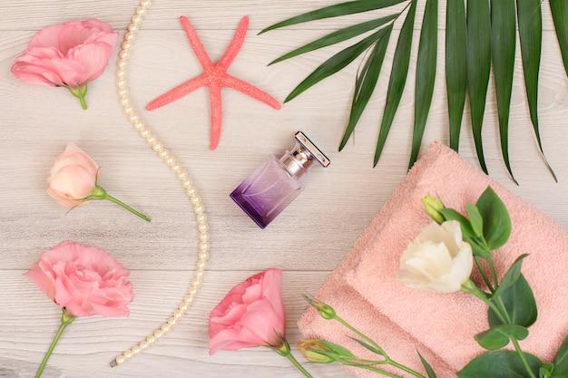 Pilha de toalhas de terry macias com flores cor de rosa, frasco de perfume, estrela do mar e folhas verdes sobre fundo de madeira. produtos de spa. vista do topo.