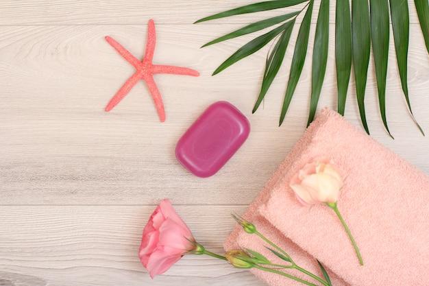 Pilha de toalhas de terry macias com flores cor de rosa, sabonete, estrela do mar e folhas verdes em fundo de madeira. produtos de spa. vista do topo.