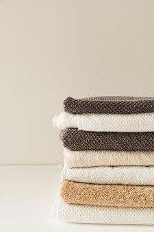 Pilha de toalhas dobradas em fundo branco. cuidados de saúde, higiene, composição de bem-estar.