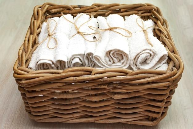 Pilha de toalhas felpudas limpas brancas em uma cesta de vime em uma cesta de madeira natural. fechar-se. foco seletivo suave. espaço da cópia do texto.