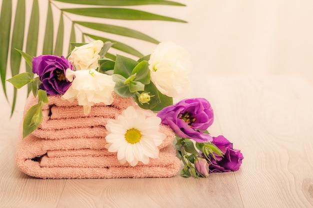 Pilha de toalhas felpudas macias com flores brancas e violetas e folhas verdes em fundo rosa