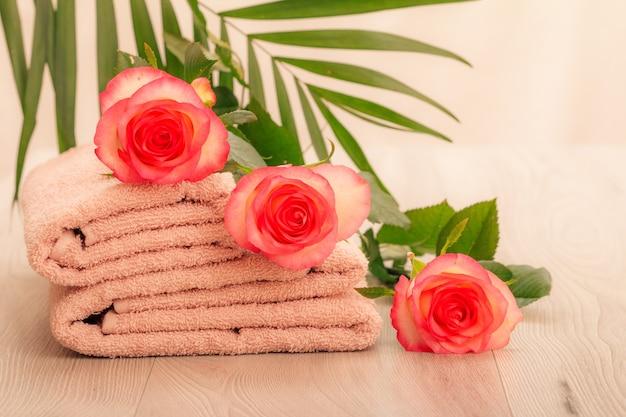 Pilha de toalhas felpudas macias com flores rosas vermelhas e folhas verdes em fundo rosa