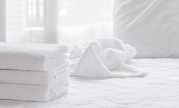 Pilha de toalhas limpas dobradas nas folhas de cama brancas no quarto moderno.