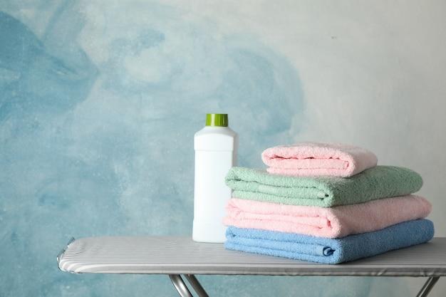Pilha de toalhas limpas e líquido de lavar roupa na tábua,