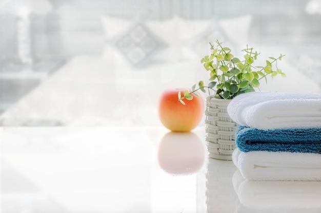 Pilha de toalhas limpas na tabela branca com borrão da sala da cama, espaço da cópia para a exposição do produto.