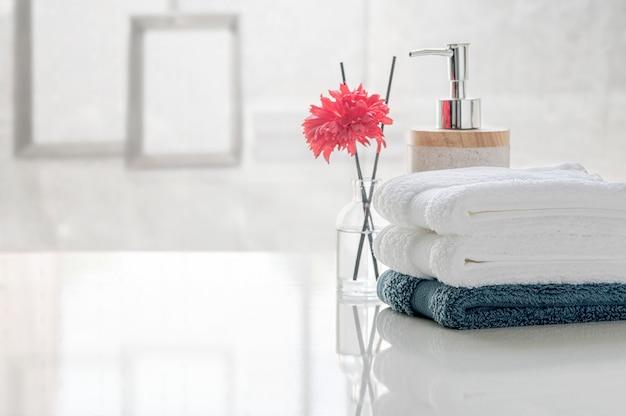 Pilha de toalhas limpas na tabela branca com borrão da sala de visitas, espaço da cópia para a exposição do produto.