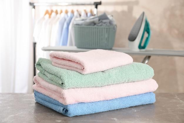 Pilha de toalhas limpas na tábua de passar roupa,