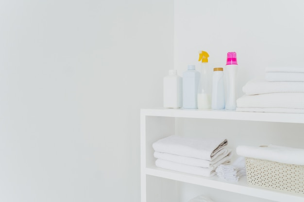 Pilha de toalhas macias brancas com líquido condicionador macio