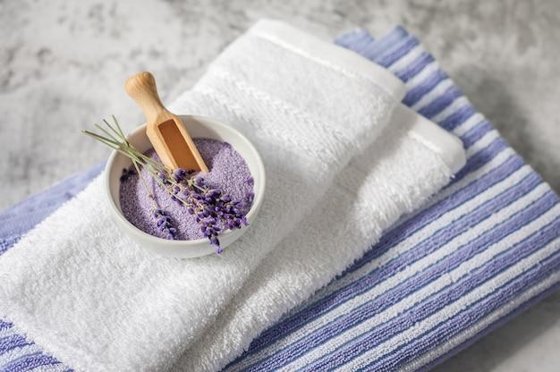 Pilha de toalhas macias limpas com um monte de alfazema e sal de banho em cinza claro. toalhas de spa contra uma parede texturizada. minimalismo, foco suave.