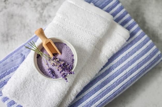Pilha de toalhas macias limpas com um monte de alfazema e sal de banho em cinza claro.