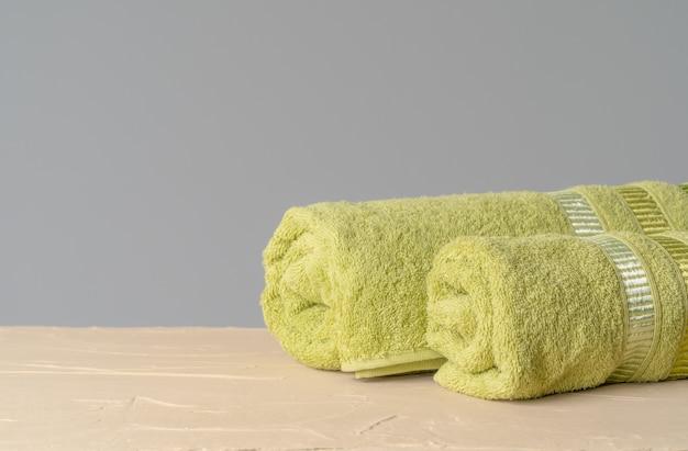 Pilha de toalhas novas e limpas contra parede cinza