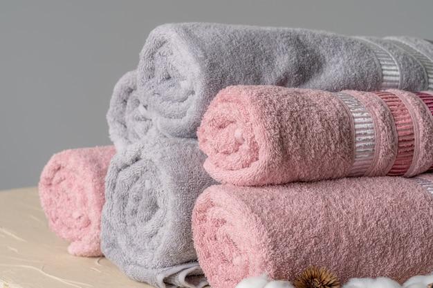 Pilha de toalhas novas limpas contra parede cinza