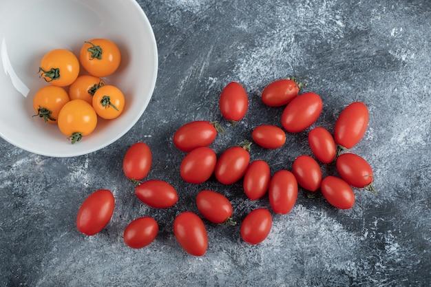Pilha de tomates-cereja frescos em fundo cinza.