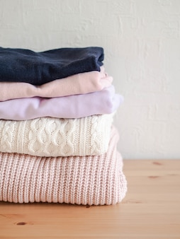 Pilha de tons pastel de blusas de lã tricotadas quentes e azul escuro na mesa de madeira