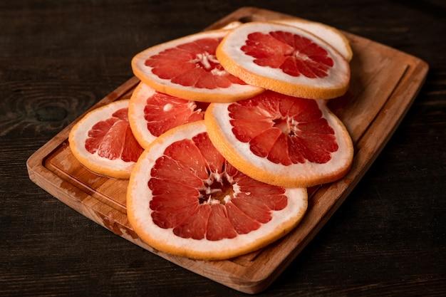 Pilha de toranja fresca fatiada em uma placa de madeira pronta para ser colocada no secador de frutas domésticas para fazer provisões de frutas cítricas cristalizadas para o inverno