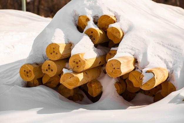 Pilha de toras de madeira caídas no chão sob a neve no inverno colhendo para uma casa ecológica
