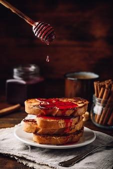 Pilha de torradas francesas com calda de frutas vermelhas no prato branco