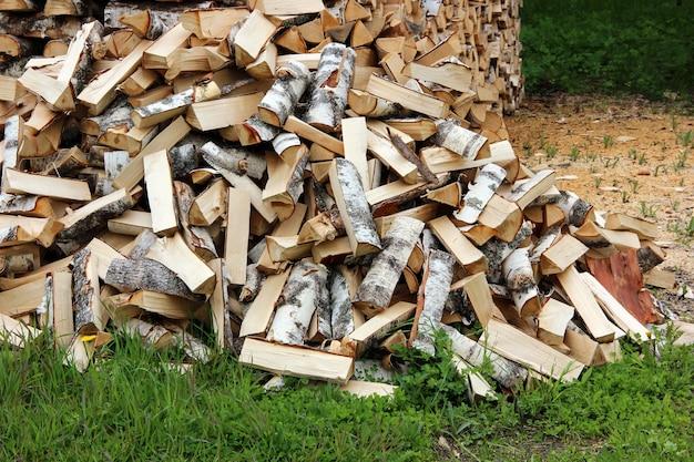 Pilha de troncos na grama, picada por um machado