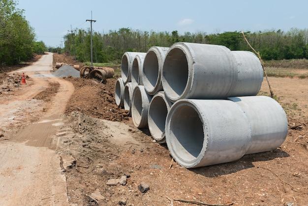 Pilha de tubo de concreto de drenagem perto da estrada em plano de fundo urbano da natureza