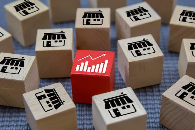 Pilha de um blogue de madeira do brinquedo da forma do cubo com a loja e o gráfico dos ícones do negócio da franquia para o crescimento e o conceito da gestão organizacional.