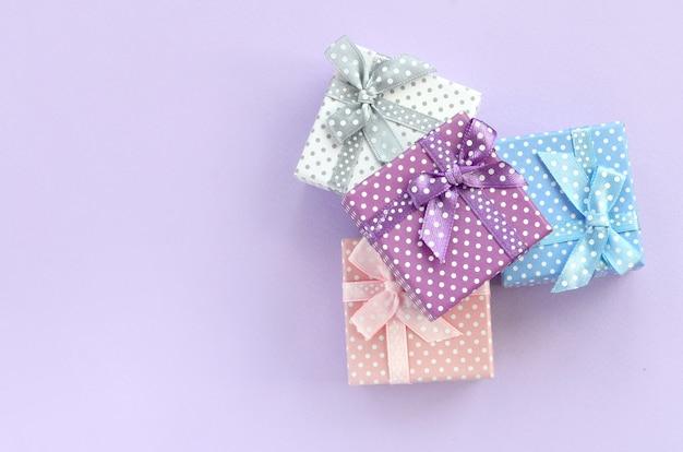 Pilha de um pequeno colorido caixas de presente com fitas encontra-se em um fundo violeta